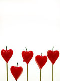 Five candles. Five red heart shape candles isolated on white Stock Photo