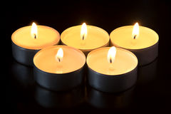 Five candles glowing in the dark Stock Images