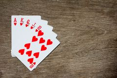 Five card of red heart royal straight flush on wood background Royalty Free Stock Photography