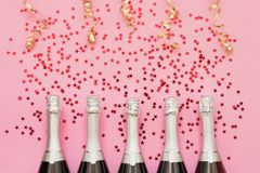 Five Champagne bottles with confetti stars and party streamers on pink background. Copy space,top view. Party background royalty free stock image