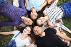 Five cheerful friends lying on grass top view portrait. Happy young women and men in casual clothes having fun outdoors. Male and female models looking at Stock Photography
