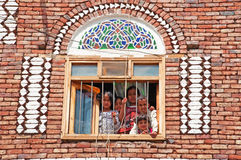 Five children, boys and girls, look out the window in a decorated house of the Old City of Sana'a, Yemen, daily life. The Old City of Sana'a, the oldest stock photos