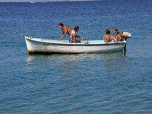 Five children in fun on boat at sea. Children (best friends) on school vacation, enjoy, swimming, sunbathing, on a small white board, while at the horizon see a Royalty Free Stock Image