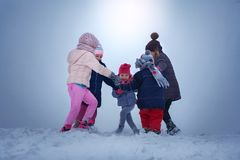 Five children are having fun in the snow. royalty free stock images