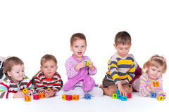 Five children playing blocks. A group of five kids with different emotions are lying or sitting and playing colorful blocks; isolated on the white background Stock Images