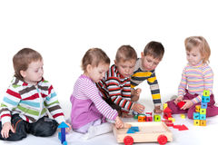 Five children playing toys. A group of five kids are playing colorful toys; isolated on the white background Stock Images