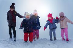 Five children are having fun in the snow. Five children run and play in a snow. Pulling sleds. Space for copy. Winter season Stock Image