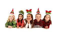 Five children in silly christmas hats laying down Royalty Free Stock Image