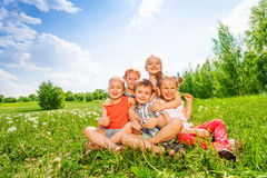Five children sit together on a meadow Stock Images