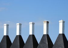 Five chimneys on a smokehouse with blue sky Stock Image