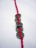 Five chinese ancient coins chained with a red cord. Five chinese Qing dynasty ancient coins chained with a red cord in one line Royalty Free Stock Images