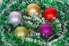 Five Christmas colored balls on the green tinsel Royalty Free Stock Photo