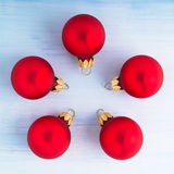 Five christmas red balls on light blue wood background top view. Stock Images