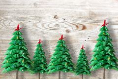 Five Christmas trees from green folded paper or origami on wooden background royalty free stock photography