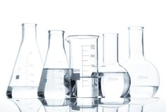 Five classic laboratory flasks with a clear liquid Stock Image