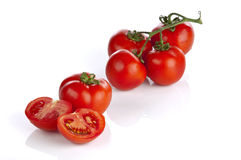 Five cluster tomatoes and one halved Stock Photos