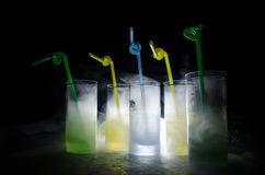 Five cocktails on the bar with smoke on dark background. Yellow, green and blue colored glasses. Stock Photo