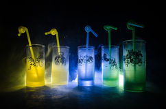 Five cocktails on the bar with smoke on dark background. Yellow, green and blue colored glasses. Royalty Free Stock Photos