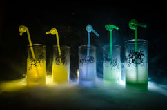 Five cocktails on the bar with smoke on dark background. Yellow, green and blue colored glasses. Stock Photography