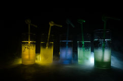 Five cocktails on the bar with smoke on dark background. Yellow, green and blue colored glasses. Stock Image