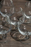 Five cognac glasses on the brown wood. With shadows Royalty Free Stock Photography