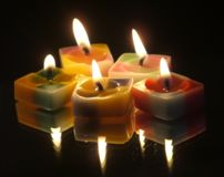 Five colored candles on a mirror Stock Photos