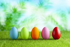 Five colored Easter eggs on short cut grass and abstract background royalty free stock photography