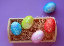 Five colorful Easter eggs in nesting box on purple background. Five Easter eggs on blue pink yellow and red in a nesting box with nesting material above shot royalty free stock image