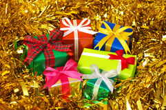 Five colorful gifts on gold tinsel.(horizontal) Stock Image