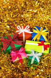 Five colorful gifts on gold tinsel.(vertical) Stock Photography