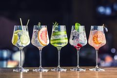 Five colorful gin tonic cocktails in wine glasses on bar counter. In pup or restaurant