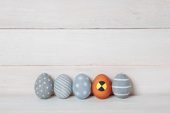 Five colorful handmade Easter eggs on a wooden background, one made in the form of a dummy for crash tests Royalty Free Stock Photo