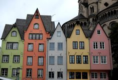 Five colorful homes and a large tower in the center of Cologne in Germany Royalty Free Stock Images