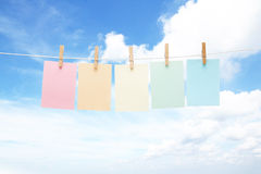 Five colorful pastel notes on pegs Stock Images