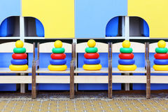 Five colorful pyramid toys stand at chairs Stock Photo