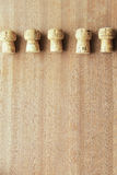 Five corks from champagne cork oak lined in a row on top of the wooden board Stock Image