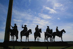 Five Cowboys. Metal figurines over blue sky Royalty Free Stock Photos