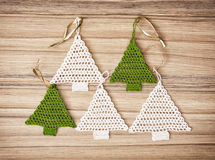 Five crochet christmas trees on the wooden background Stock Photos