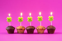 Five Cupcakes with burning candles over a pink background. Stock Photo