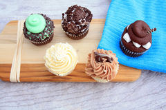 Five cupcakes on cutting board on wooden background Royalty Free Stock Images