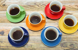 Five Cups. Five coffee cups of various colors on a wooden surface Stock Images