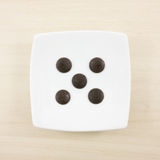 The five dark chocolate buttons and small white square disk Stock Photos