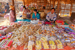 Five-day market, Inle Lake. Heho, Myanmar - March 03, 2011 - Man and woman selling food snacks at the five-day market near Inle Lake Stock Photos
