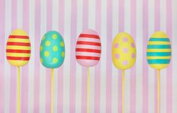 Five decorated colourful Easter eggs on a pink striped background stock photography