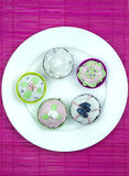 Five decorated muffins  on a wooden and pink placemat Stock Photo