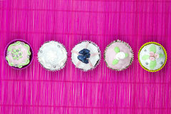 Five decorated muffins  on a wooden and pink placemat Stock Images