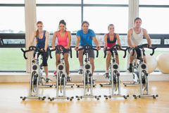 Five determined people working out at spinning class Stock Image