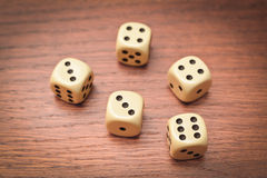 Five dice on a wooden table Royalty Free Stock Photo