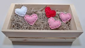Five different colored cloth hearts in a wooden box stock image