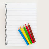 Five different colors pencil on empty clear page of notebook Royalty Free Stock Photo